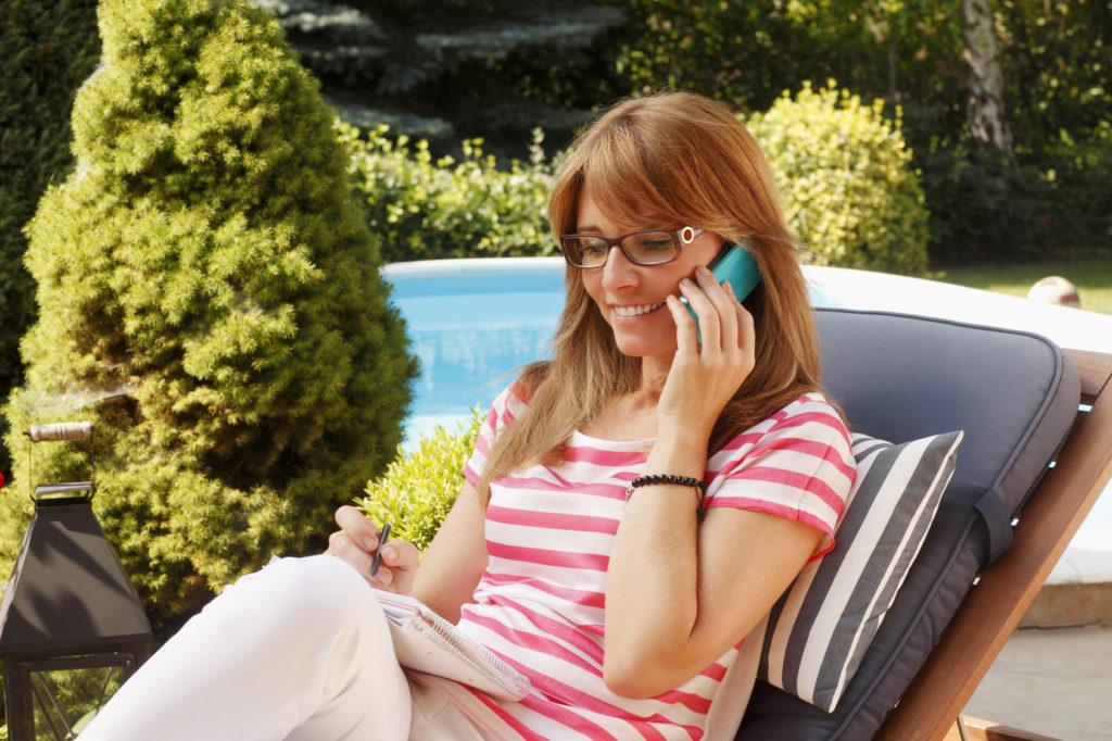 Frau telefoniert mit Festnetztelefon im Garten